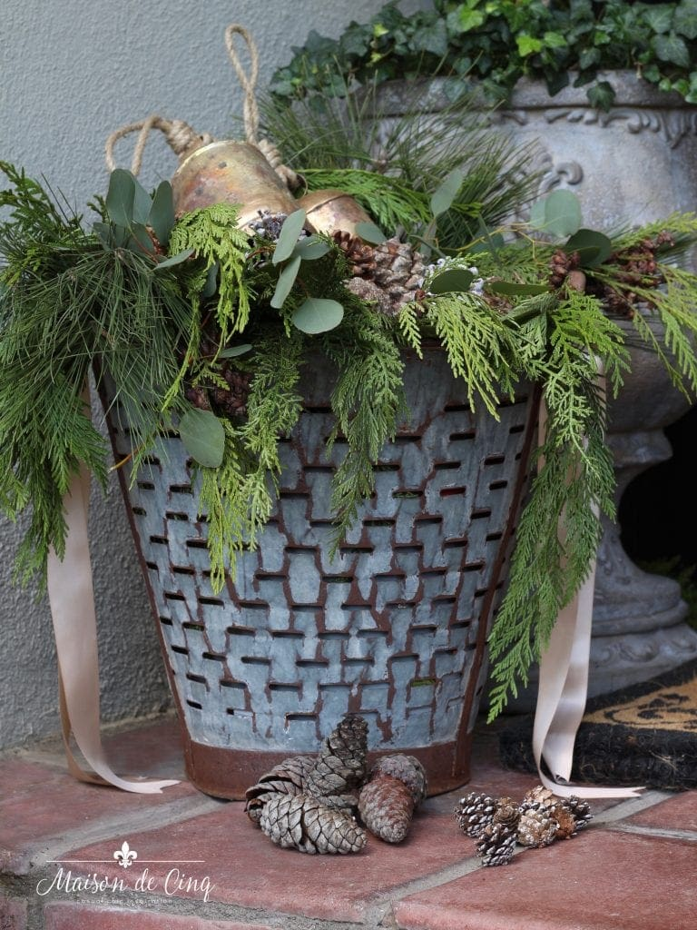 vintage olive bucket with greens pine cones and brass bells gorgeous holiday christmas decor