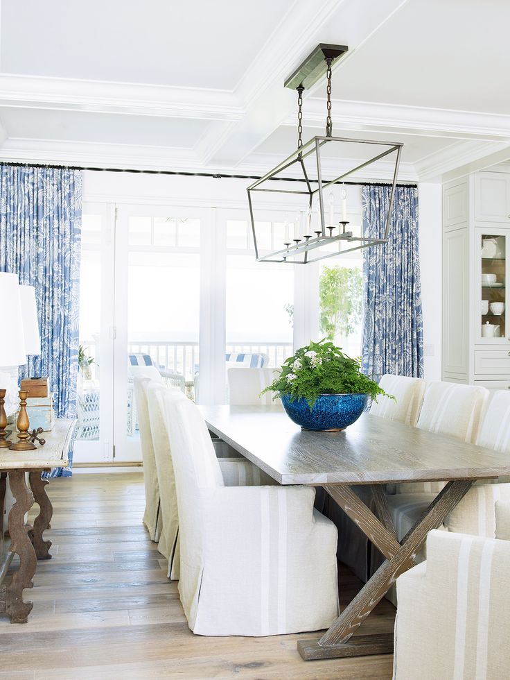 blue and white curtains modern farmhouse dining room slipcovered chairs blue vase chandelier