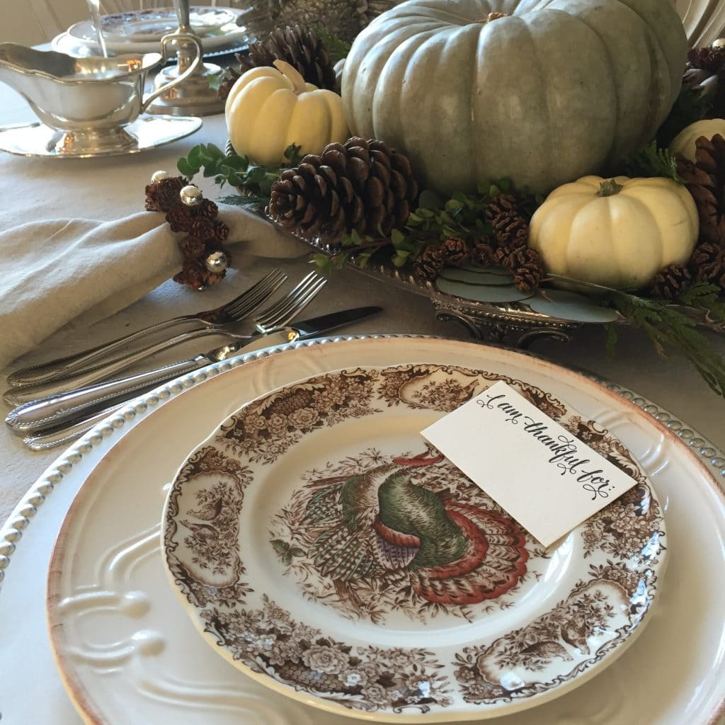 thanksgiving tablescape with transferware turkey plates pinecones and pumpkins