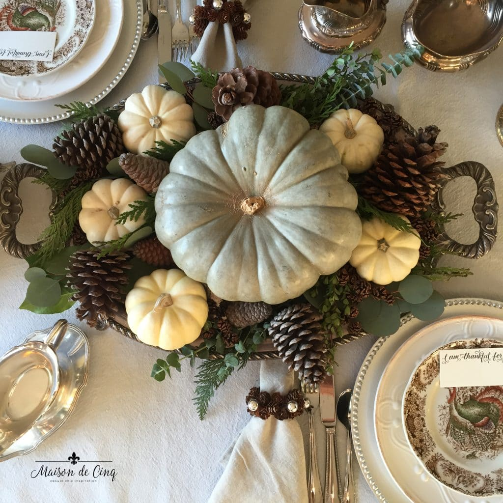 thanksgiving tablescape silver tray holds green and white pumpkins with eucalyptus and pine sprigs