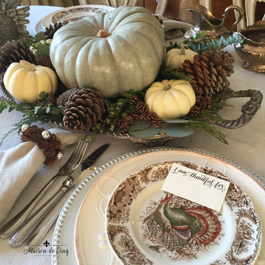 thanksgiving tablescape silver tray holds green and white pumpkins and pinecones