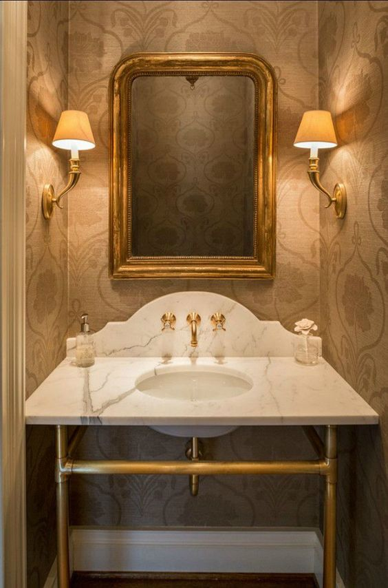 powder room with gold mirror faucet and sconces