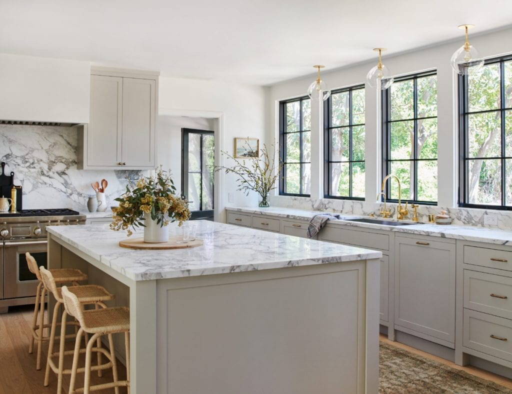 stunning white kitchen featuring brass hardware trend and marble counters and brass lighting