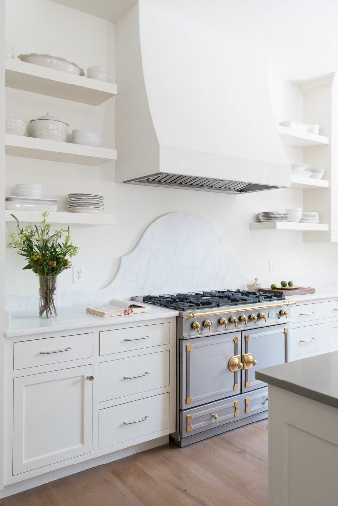 white kitchen marble backsplash brass la cornue stove