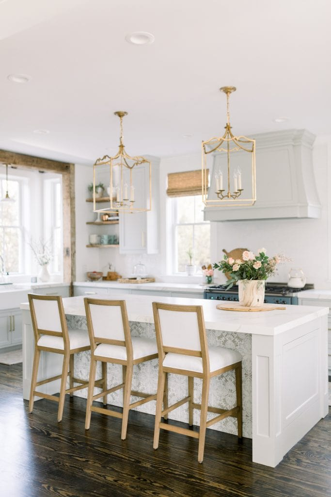 white and grey kitchen with gold hardware and lanterns