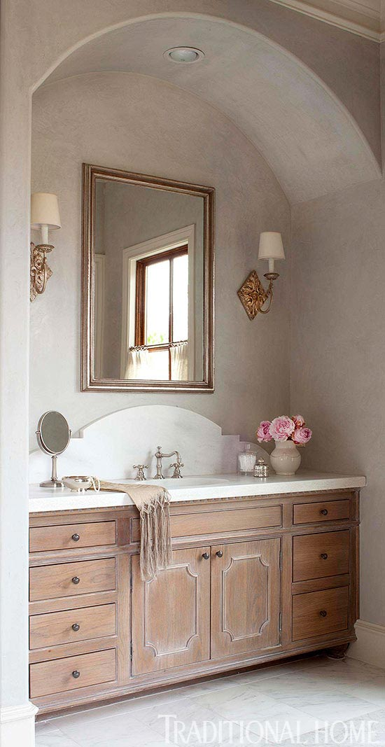 gorgeous bathroom with marble backsplash and gold sconces