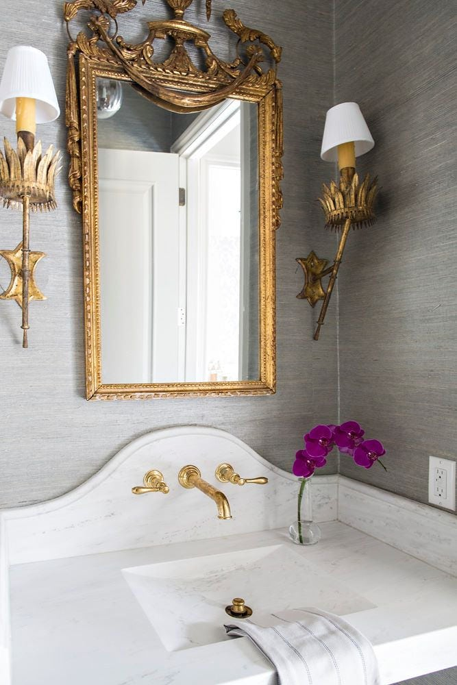 grey and gold bathroom with stunning antique mirror sconces and pedestal sink