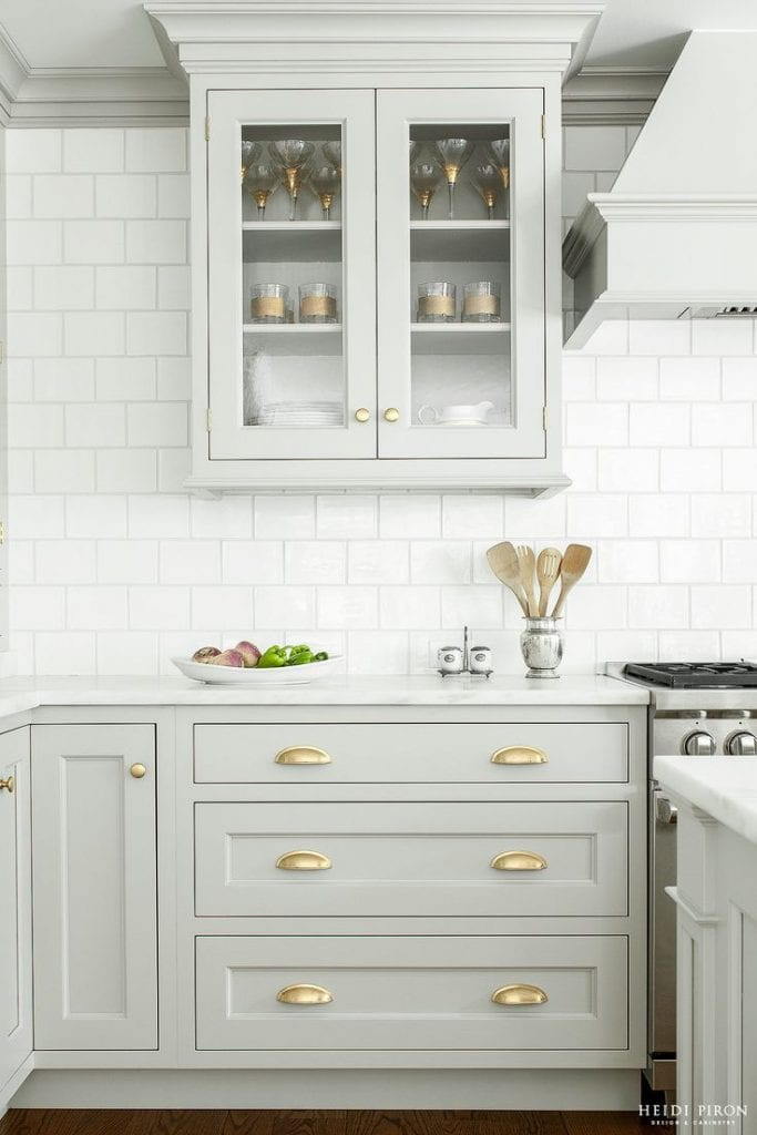 grey and gold kitchen subway tile glass cabinets brass hardware