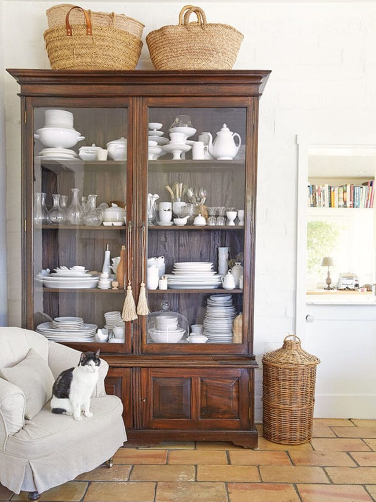 antique baskets on top of armoire white ironstone white walls charming farmhouse style