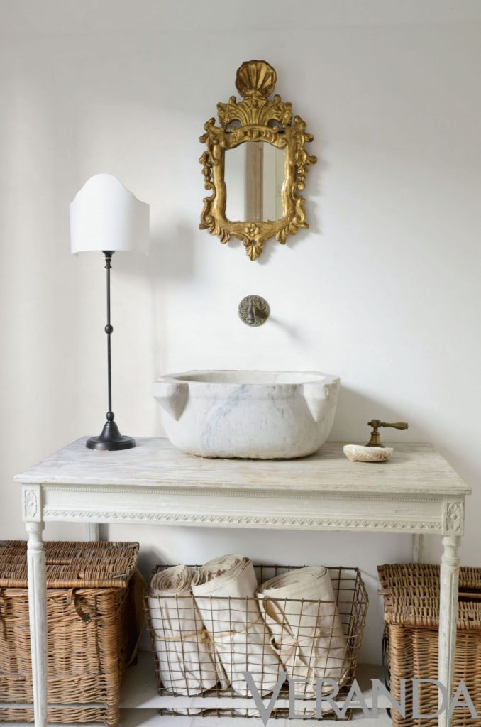 antique baskets under bathroom console with stone sink gold mirror french country style gorgeous