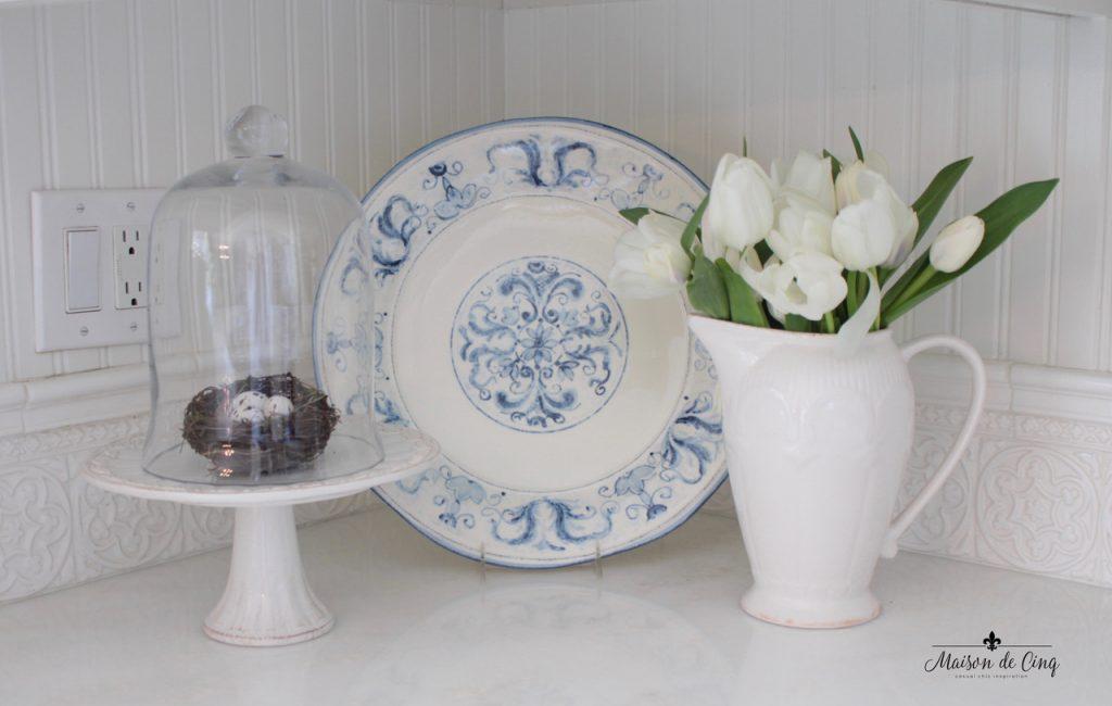 decorating cloches white kitchen farmhouse style bird's nest under glass blue plate vase white tulips