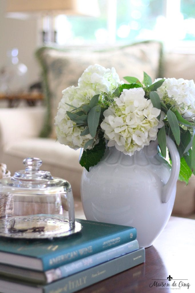 decorating cloches key under glass and white ironstone pitcher on coffee table vignette french country