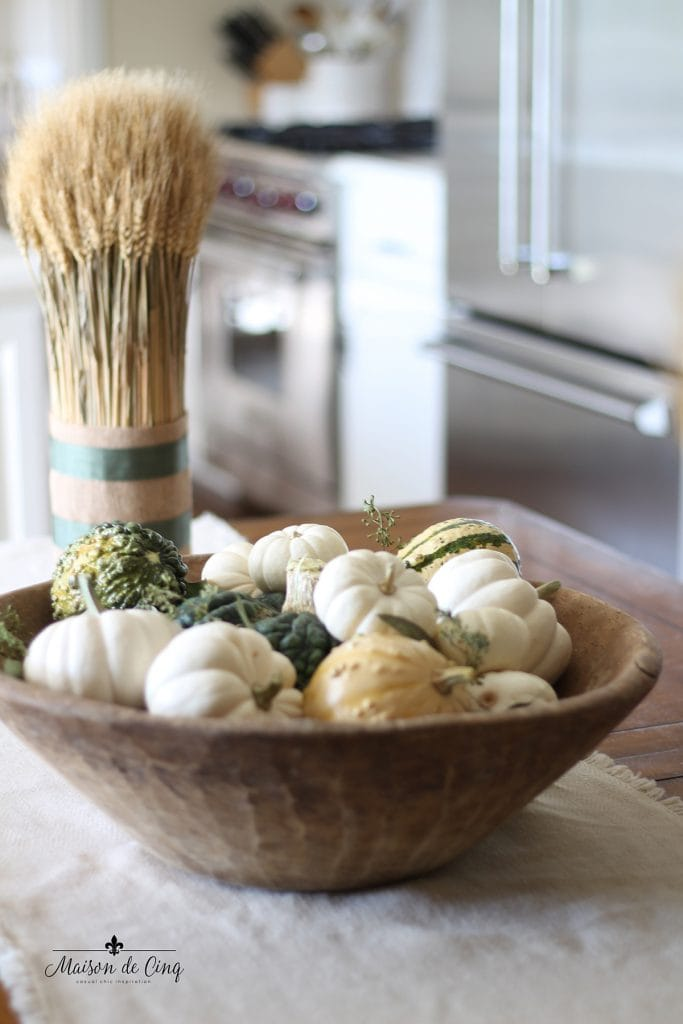 dough bowl holding gourds and baby boo pumpkins with wheat shafts tablescape fall decorating idea