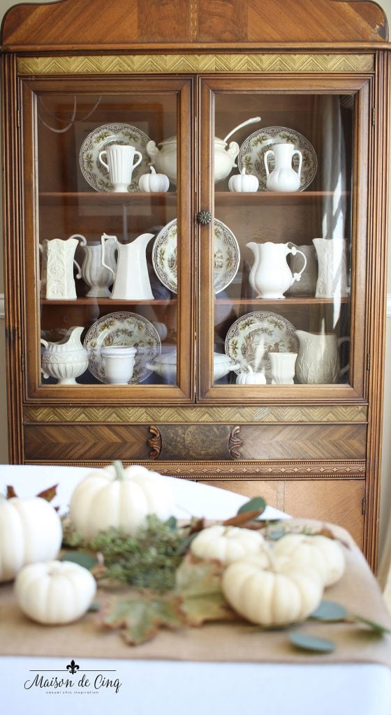 cabinet filled with white ironstone and brown transferware fall decor