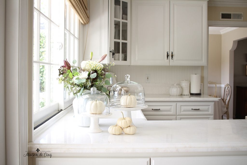 neutral fall decor in white farmhouse kitchen pumpkins on cake stands and fall flowers