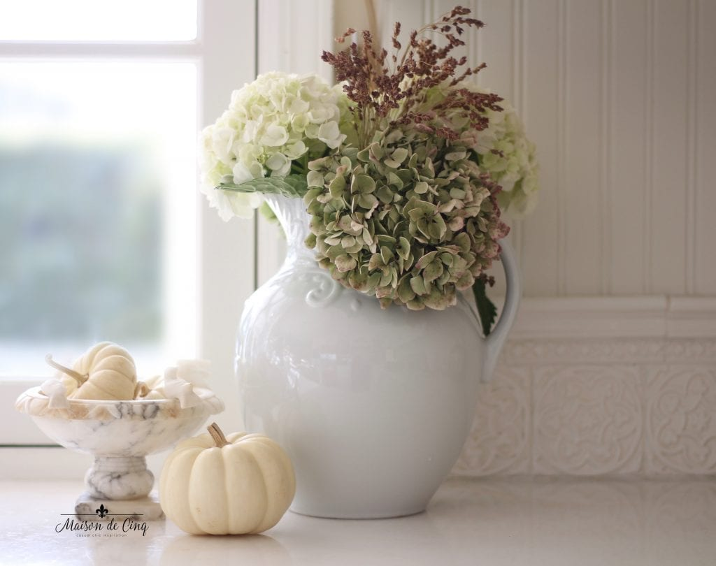 neutral fall decor white pitcher with hydrangeas and white pumpkins on counter