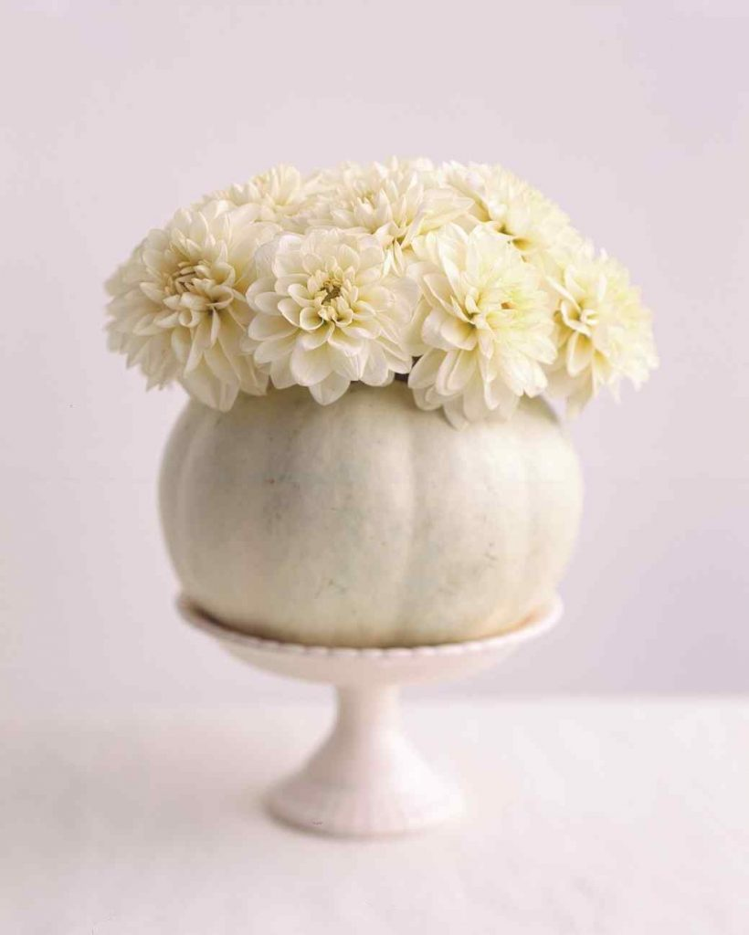 white pumpkin centerpiece with white mums on cake stand vintage charm