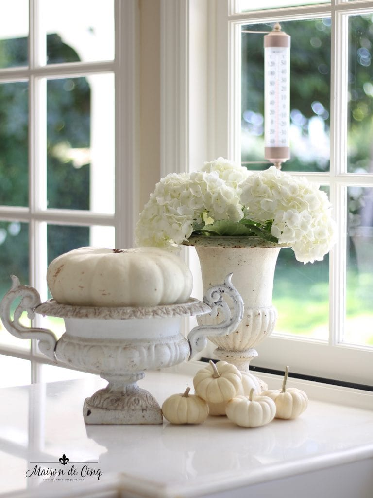 white pumpkins in vintage white chippy french urns with hydrangeas french country style kitchen fall decor
