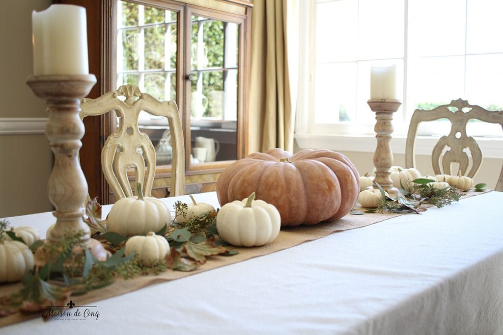 beautiful fall table display with pumpkins greens and wood candleholders