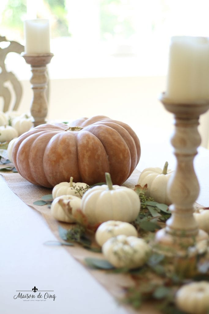 white pumpkins wood candle holders and leaves create gorgeous fall decor