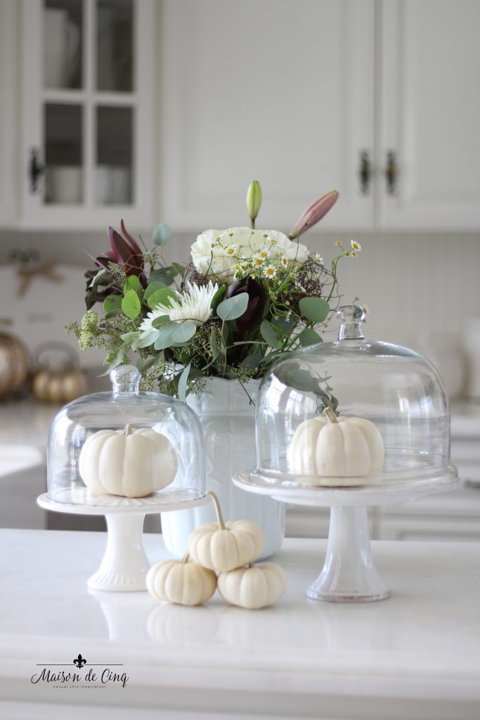 neutral fall decor white pumpkins in cloches with fall flowers in farmhouse kitchen
