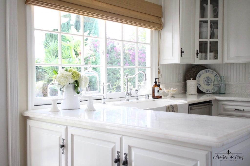 kitchen renovation french country style gorgeous windows farmhouse sink marble counters glass cabinets flowers