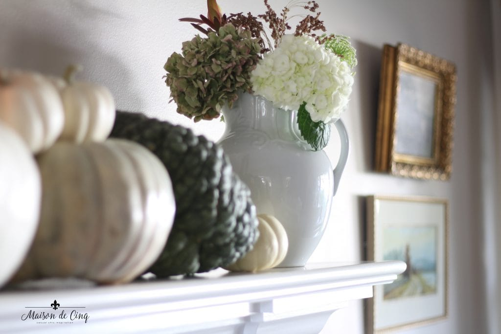 neutral fall decor mantel with pumpkins and hydrangeas