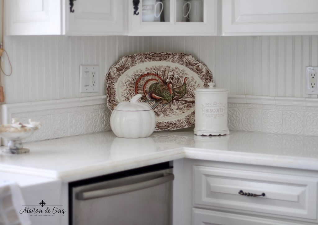 vintage turkey plates platter in white french country farmhouse kitchen beadboard backsplash marble counters
