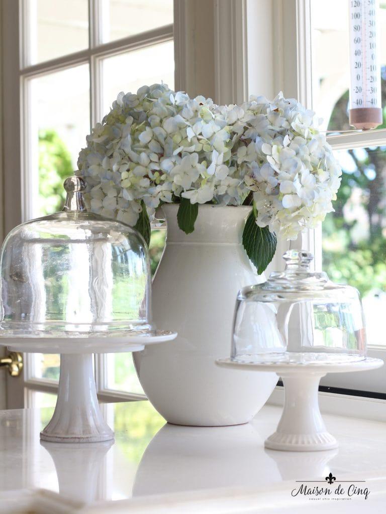 decorating cloches white cake stands hydrangeas in white pitcher kitchen counter vignette