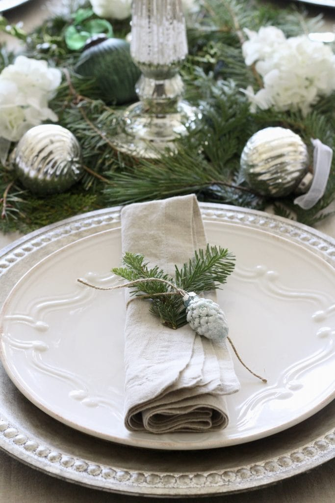holiday tablescape gorgeous with ornaments silver chargers and greens