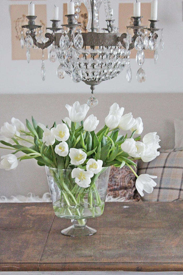 white tulips in glass vase on dining table French farmhouse charm
