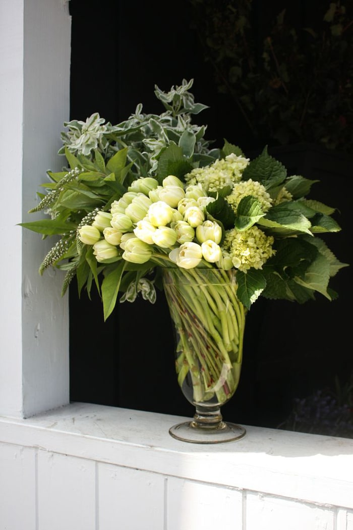 stunning arrangement of white tulips with greens in glass vase