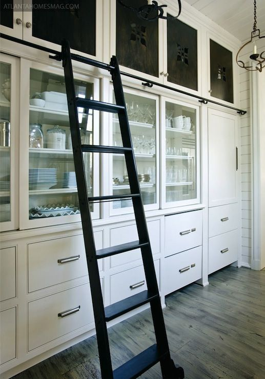 butlers-pantry with white cabinets and black library ladder