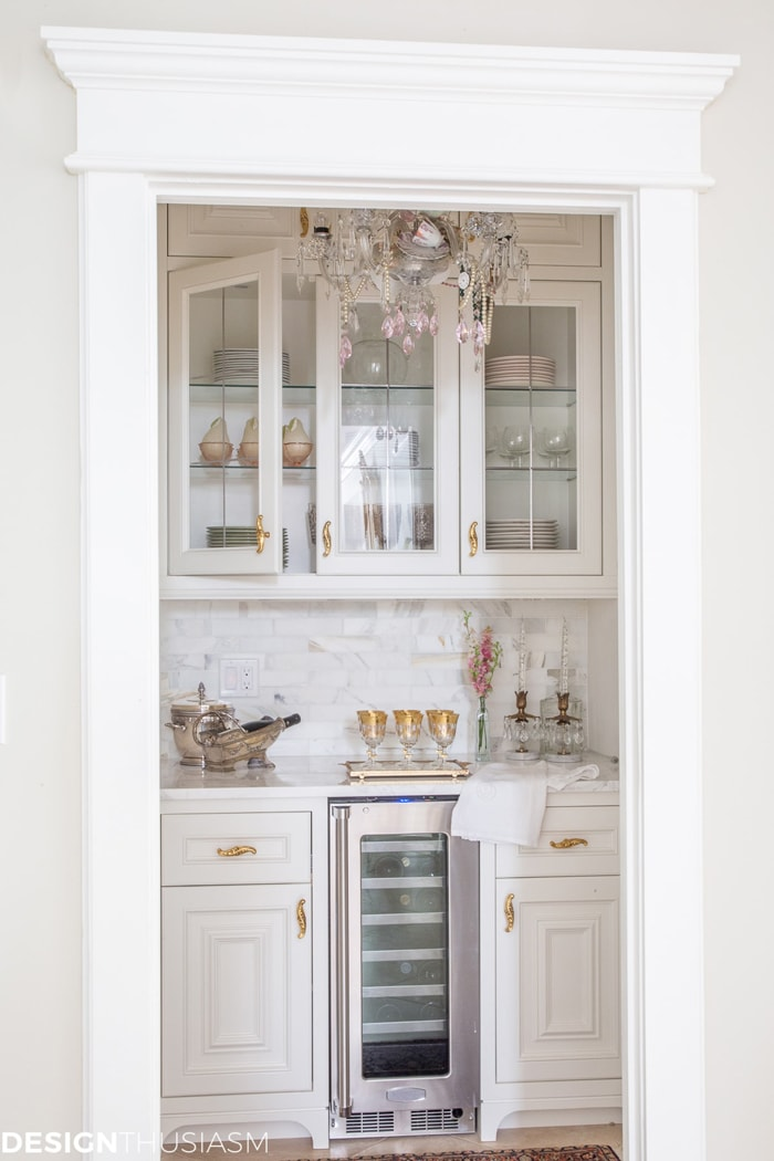 butler's pantry from closet with glass cabinets and marble backsplash
