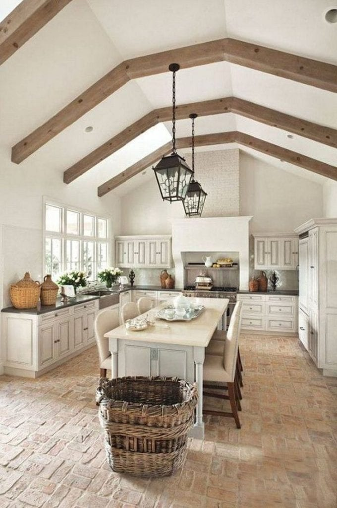 french farmhouse kitchens wood ceiling beams antique lanterns baskets demijohns marble island