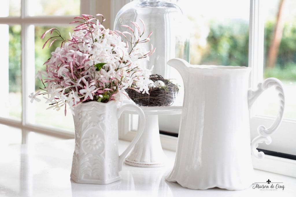 decorating with flowers jasmine in white pitcher with cake stand and cloche on kitchen counter