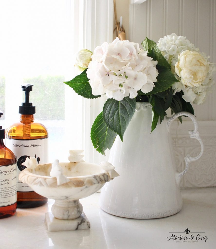 decorating with flowers white pitcher with white marble bowl on counter in farmhouse kitchen