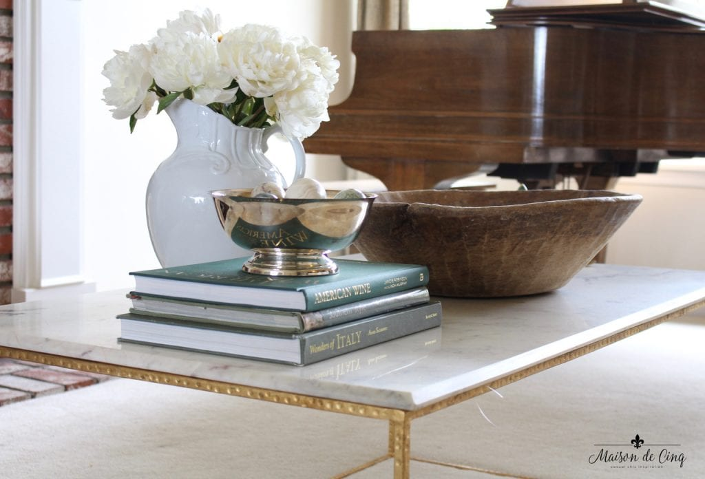 decorating with flowers peonies in white pitcher on coffee table bowl books