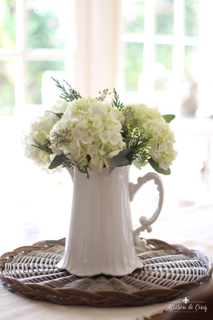 decorating with flowers hydrangeas in white pitcher on top of basket tray