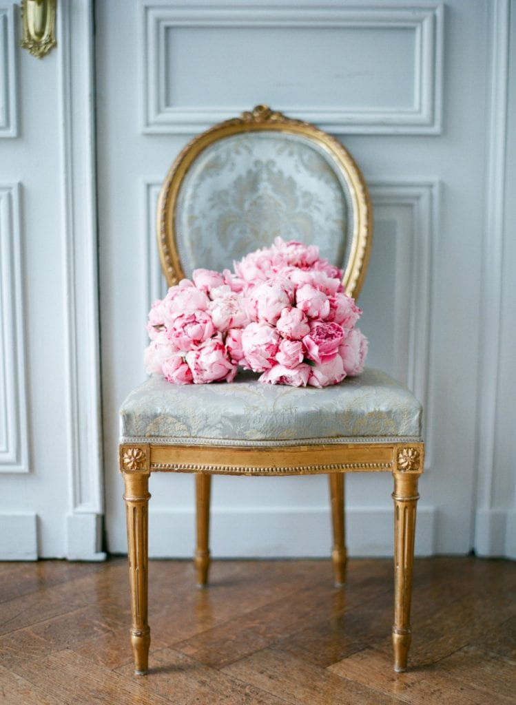 pink peonies on gorgeous french chair wood floors paneled door vignette still life