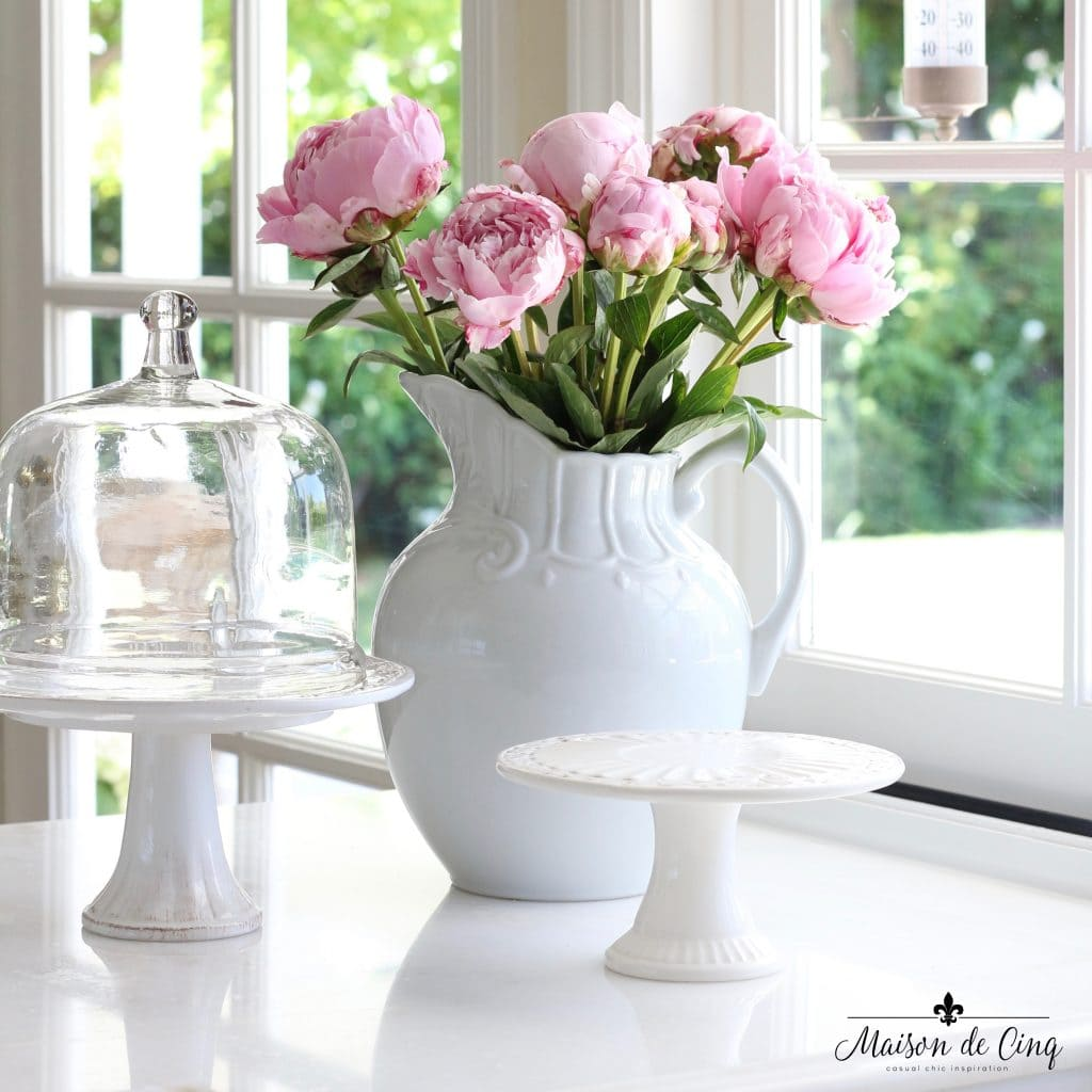 pink peonies in white ironstone pitcher still life in white kitchen with cloches and cake stands