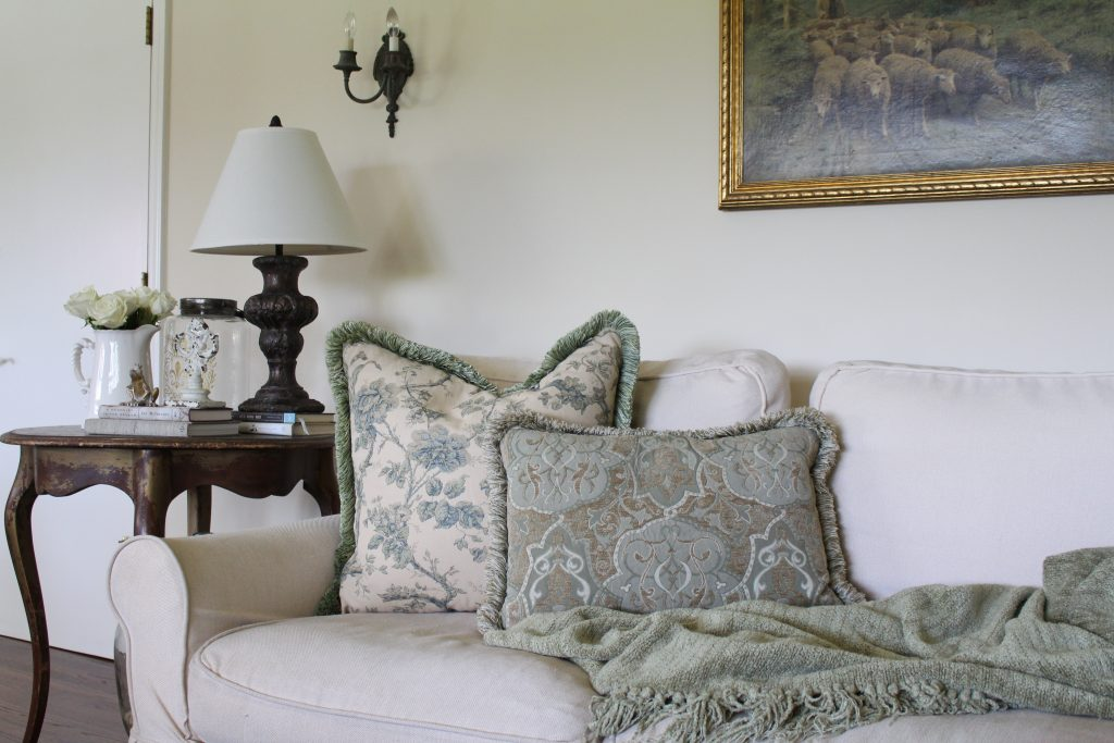 family room green pillows cream sofa antiques