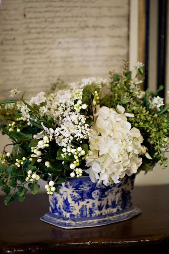 white hydrangeas blue and white vase white berries