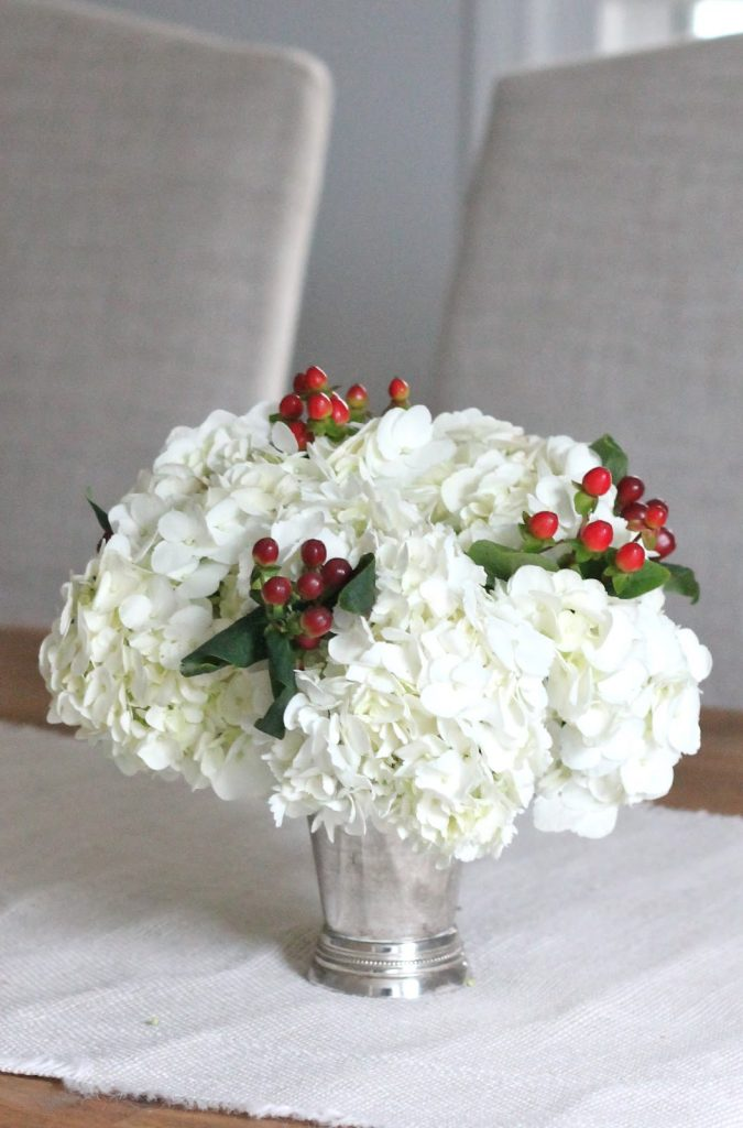 white hydrangeas red berries green leaves christmas arrangement centerpiece
