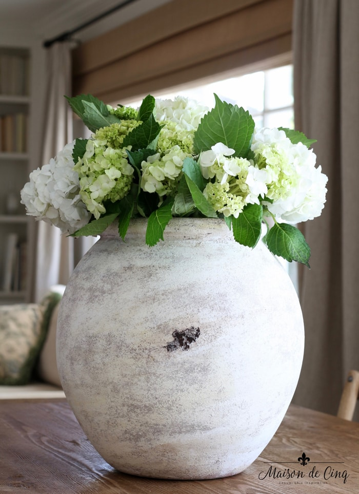 decorating with white hydrangeas in antique olive jar floral decor display