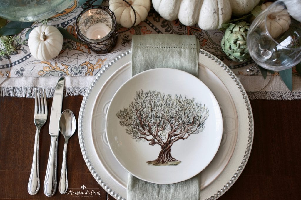 elegant fall tablescape fall plate with tree silver charger and artichokes and pumpkins