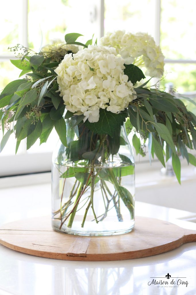 white hydrangeas eucalyptus flower arrangement kitchen counter wood bread board