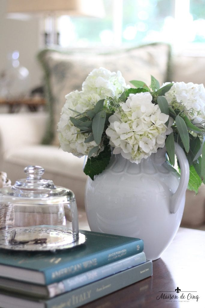 white hydrangeas ironstone pitcher sweet vignette books cloche