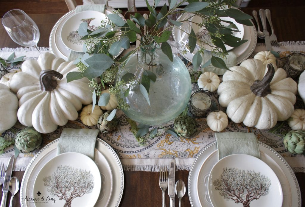elegant fall tablescape with eucalyptus in demijohn and white pumpkins