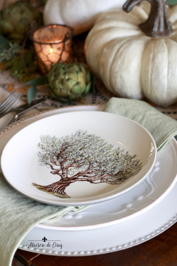 elegant fall tablescape with plate with tree candles artichokes and white pumpkin